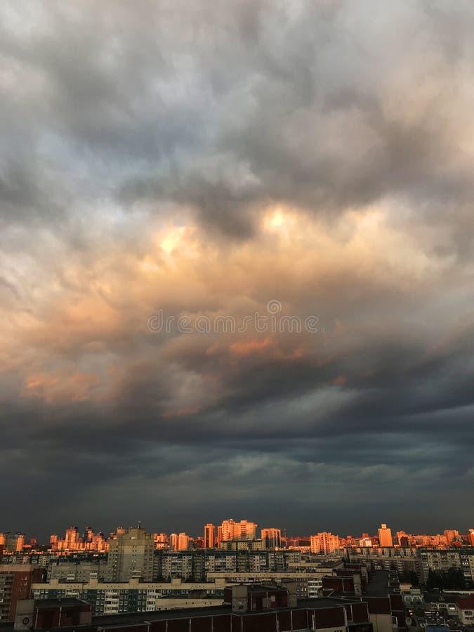 Nuvens escuras sobre os telhados de prédios altos O céu antes de uma tempestade ou furacão fotografia de stock