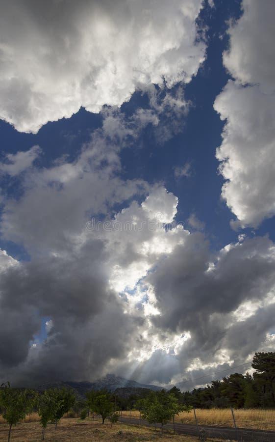Nuvens gigantes Cumulus e raios solares através de nuvens antes da tempestade de Verão que se aproxima numa aldeia da ilha grega  fotos de stock royalty free