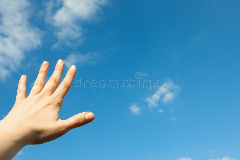 Nuvens macias brancas bonitas em um claro - fundo do céu azul com mão da mulher fotografia de stock royalty free