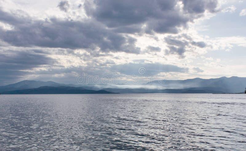 Nuvens, montes e mar em Noruega imagem de stock royalty free