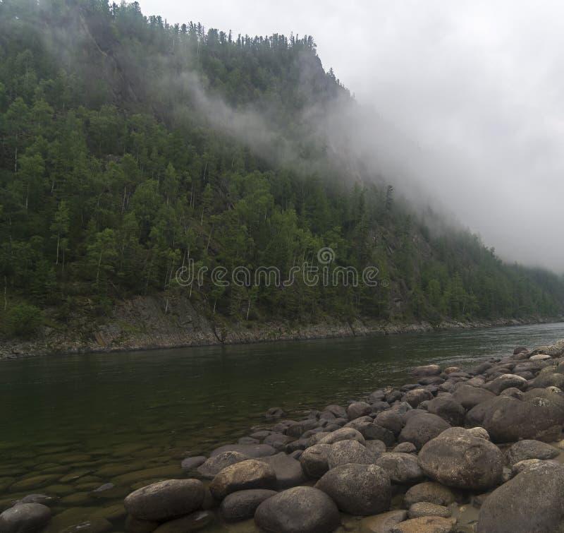 Nuvens muito baixas sobre um rio da montanha fotografia de stock