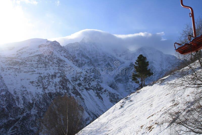 Nuvens nos picos de montanha, pinheiro na inclinação nevado e cadeira do elevador do cabo foto de stock