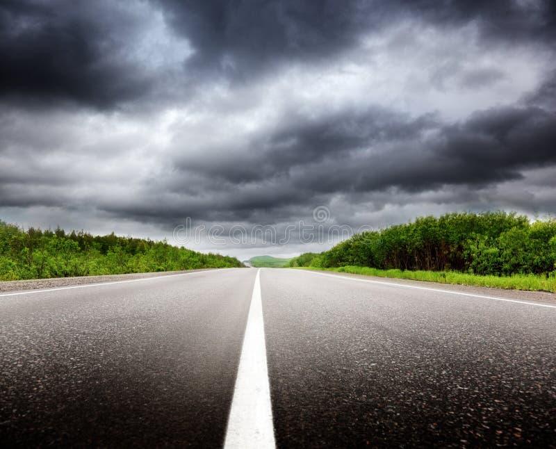 Nuvens pretas e estrada imagem de stock