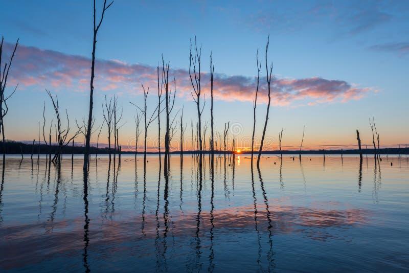 Nuvens que refletem em um lago no nascer do sol imagens de stock royalty free