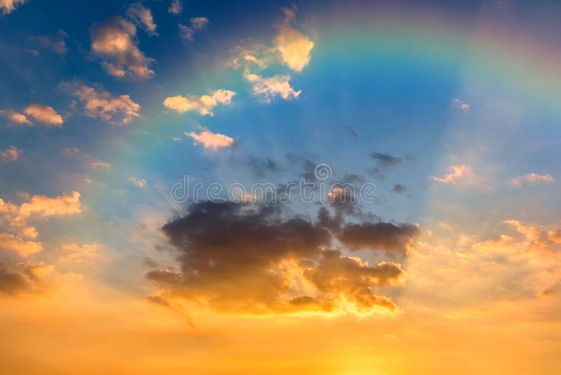 Nuvens, raios de Sun e arco-íris coloridos no céu no por do sol para o fundo natural fotografia de stock