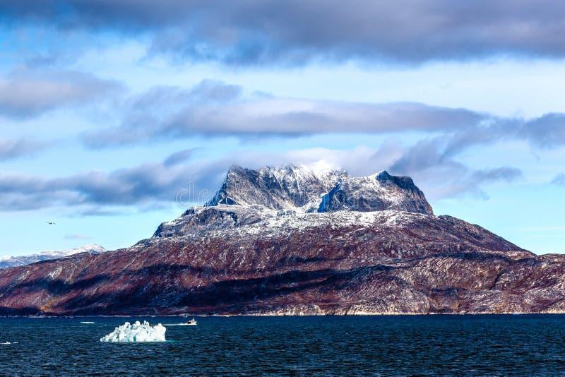 Nuvens sobre os picos de montanha de Sermitsiaq cobertos na neve com o azul fotos de stock royalty free
