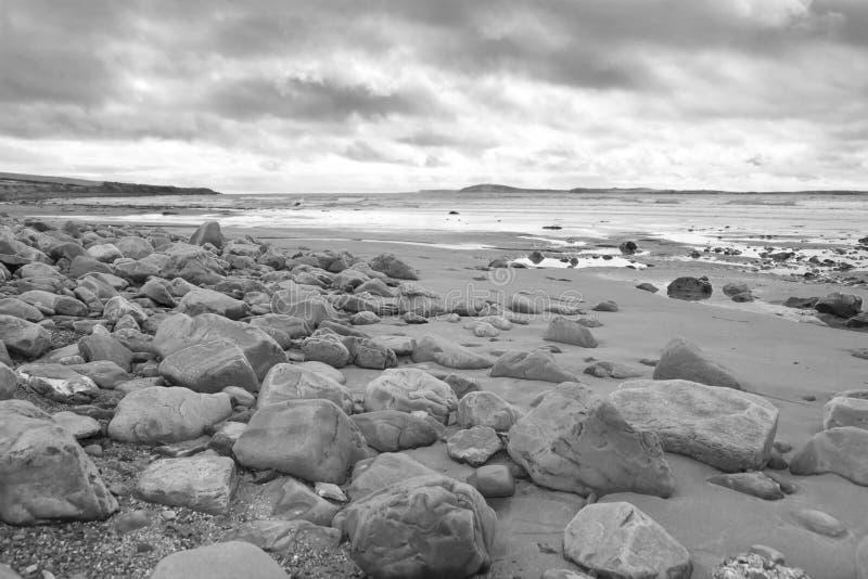 Nuvens tormentosos sobre a praia beal rochosa imagem de stock
