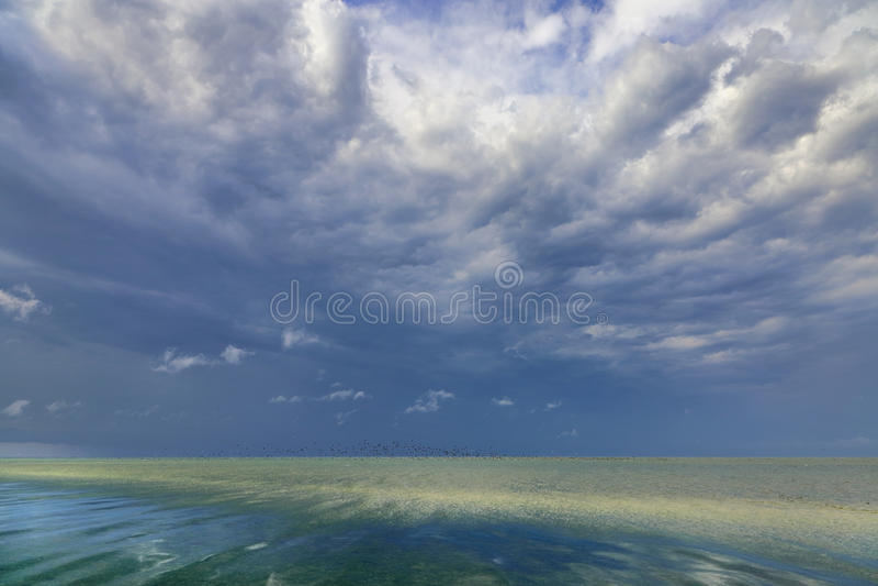 Nuvens tormentosos sobre a superfície belamente ensolarado do mar fotos de stock