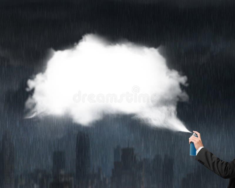Nuvola bianca di spruzzatura della mano maschio su paesaggio urbano di buio della pioggia persistente immagini stock