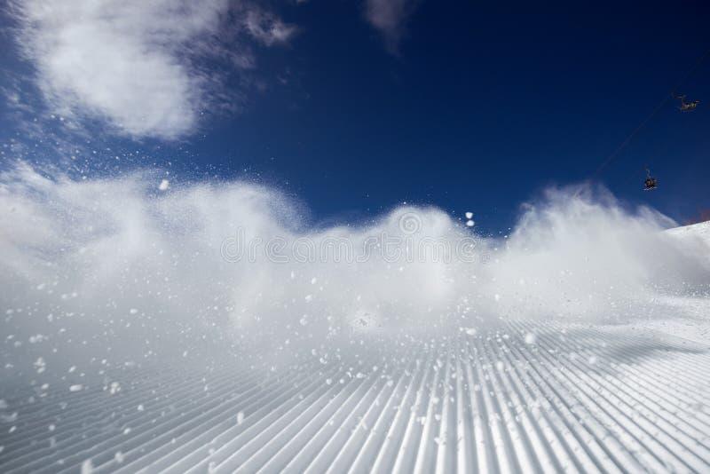 Nuvola di polvere della neve dopo lo sciatore sul pendio dello sci immagini stock libere da diritti