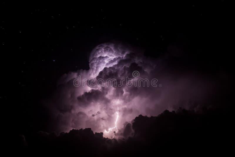 Nuvola di tempesta accesa da fulmine alla notte fotografia stock