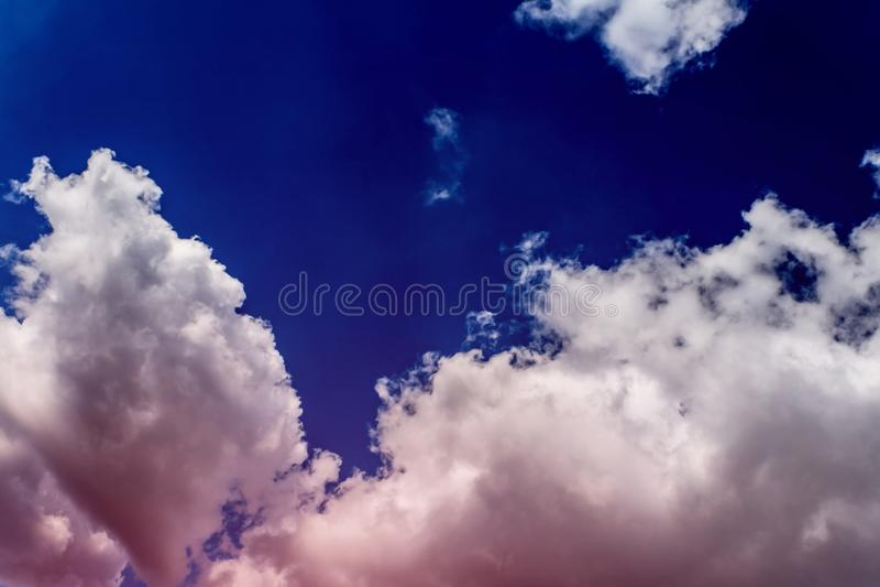 Nuvola lanuginosa rosa contro il cielo blu come il cotone della vaniglia della fragola dello zucchero, concetto dei sogni, sogni  immagine stock
