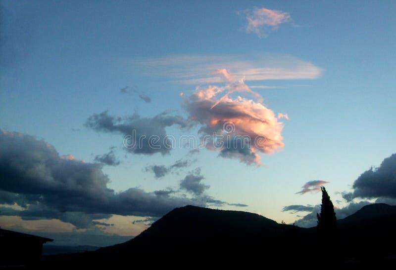 Nuvola rosa nel cielo contro lo sfondo della montagna immagine stock