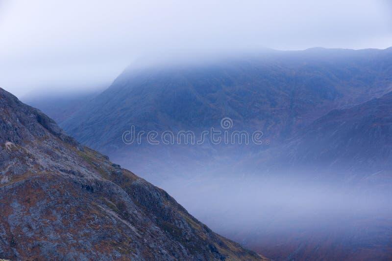 Nuvole attraverso le montagne immagine stock