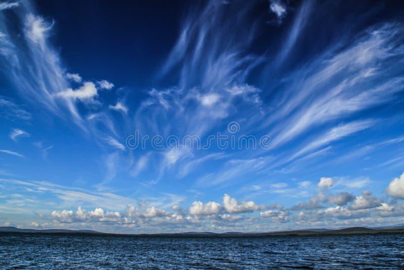 Nuvole bianche vaghe fantastiche contro un galleggiante blu scuro del cielo fotografie stock libere da diritti