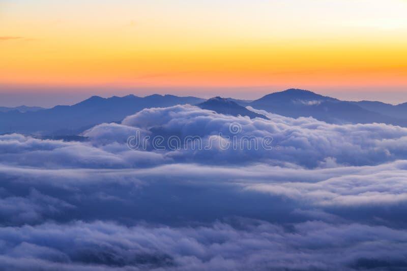 Nuvole che si rivoltano le cime delle montagne all'alba immagini stock libere da diritti