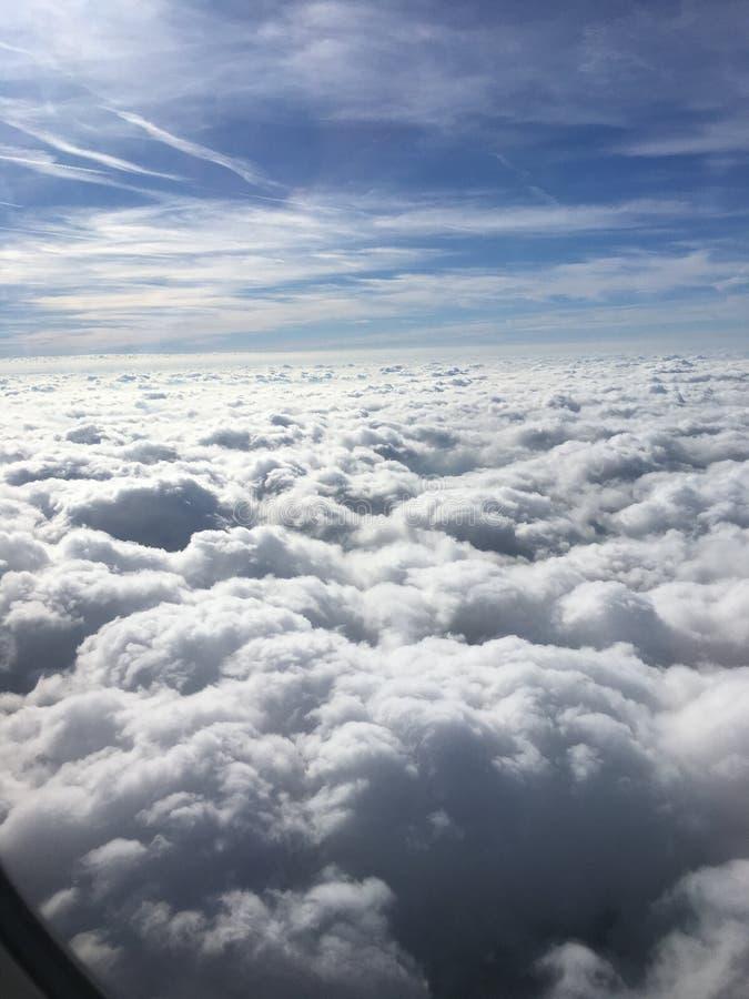 Nuvole da una finestra piana immagini stock