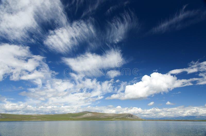 Nuvole di cirrostrato sopra il chiaro lago mongolo fotografia stock