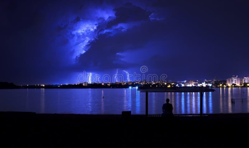 Nuvole di tempesta con fulmine e un uomo che si siede sotto un tetto sulla sponda del fiume immagini stock libere da diritti