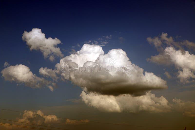 Nuvole di tempesta saturate contro il cielo scuro, tinta blu scuro immagini stock libere da diritti