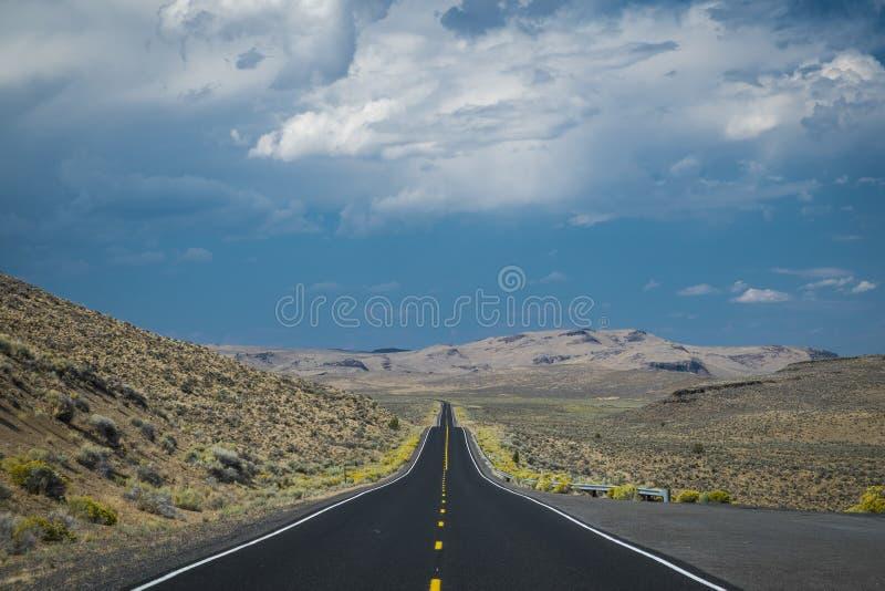 Nuvole di tempesta scure sopra la strada principale del deserto immagine stock libera da diritti