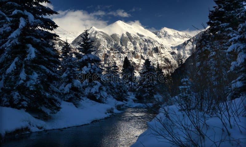 Nuvole drammatiche di inverno, neve alpina cristallina e corrente ghiacciata in Rocky Mountains, Colorado immagini stock
