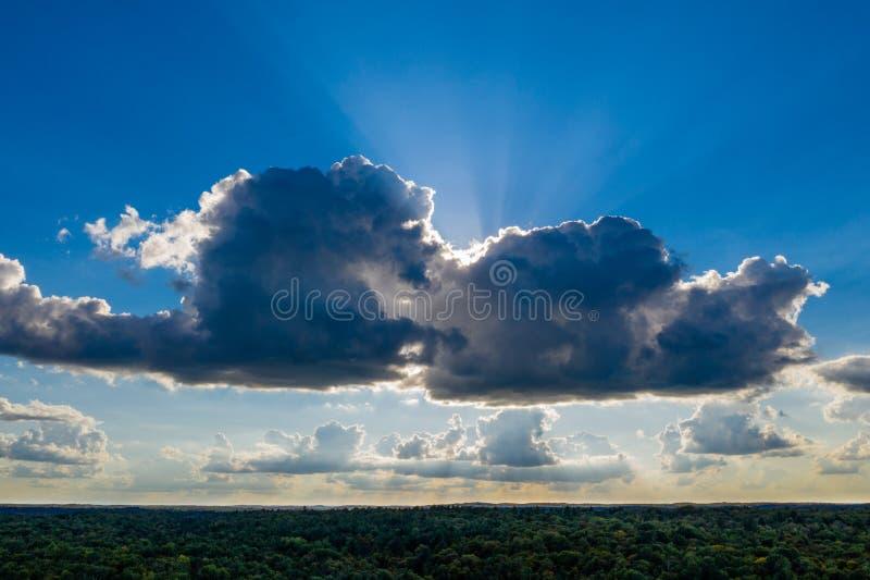 Nuvole e raggi del sole sopra una foresta fotografie stock libere da diritti