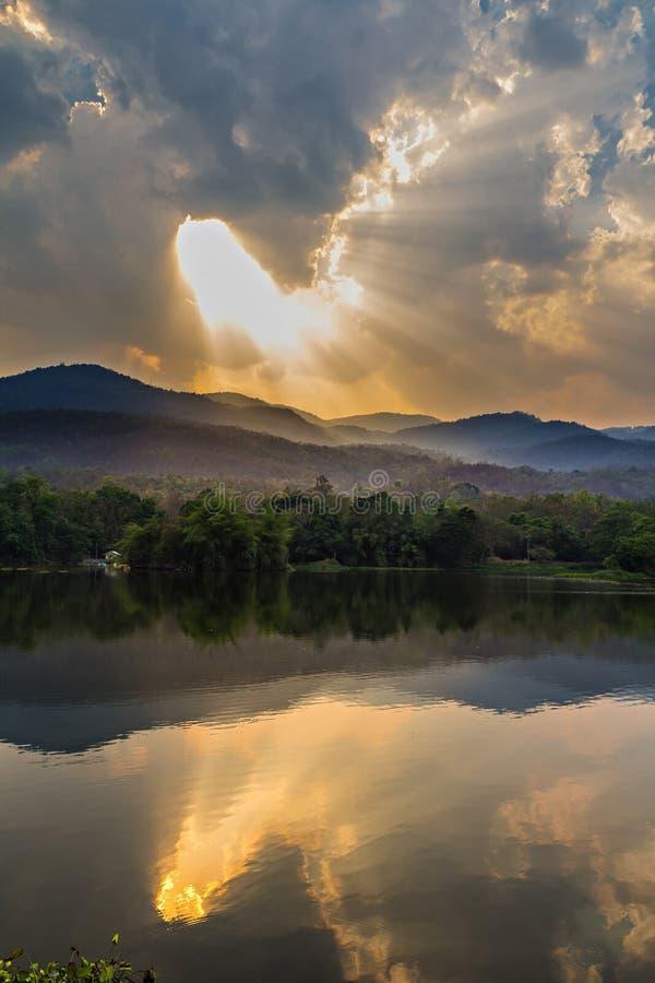 Nuvole e raggio di sole sopra la montagna immagini stock