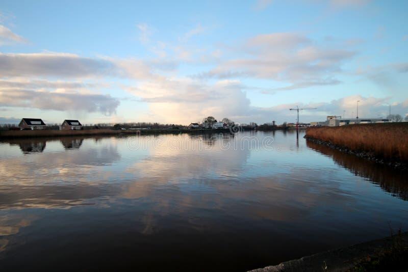 nuvole e specchi di alba sul fiume Hollandse IJssel in fotografia stock libera da diritti