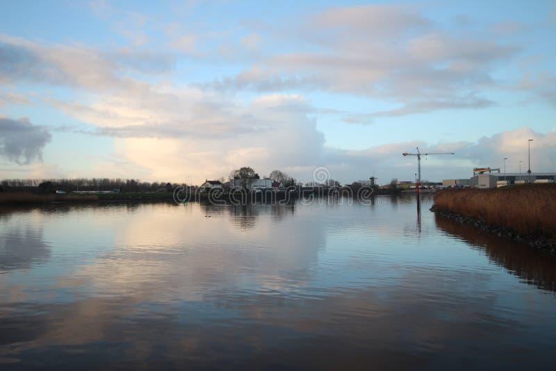 nuvole e specchi di alba sul fiume Hollandse IJssel in fotografia stock
