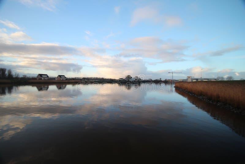 nuvole e specchi di alba sul fiume Hollandse IJssel in immagini stock libere da diritti
