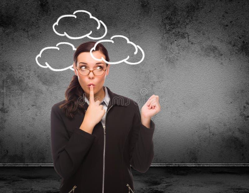 Nuvole estratte intorno alla testa di giovane donna adulta davanti alla parete con lo spazio della copia immagine stock libera da diritti