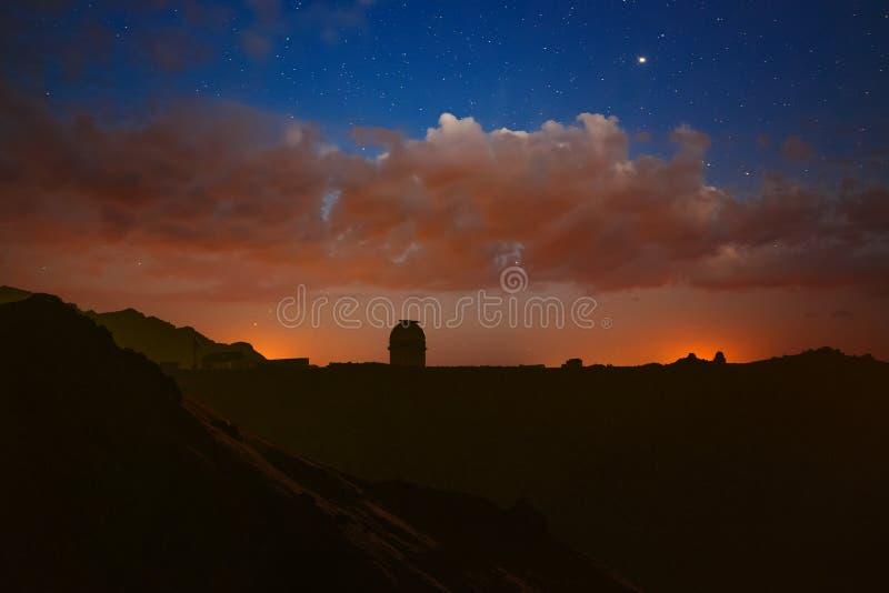 Nuvole luminose alla notte e stelle nel cielo Osservatorio nelle montagne per esplorare spazio su un fondo luminoso della Via Lat immagini stock