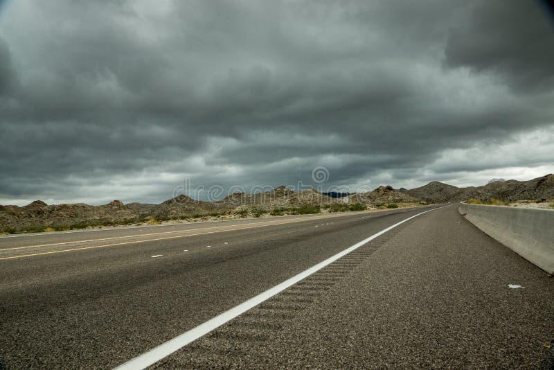 Nuvole scure, strada principale del deserto immagine stock