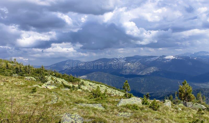 Nuvole temporalesche sopra le montagne durante l'ascesa fotografia stock libera da diritti