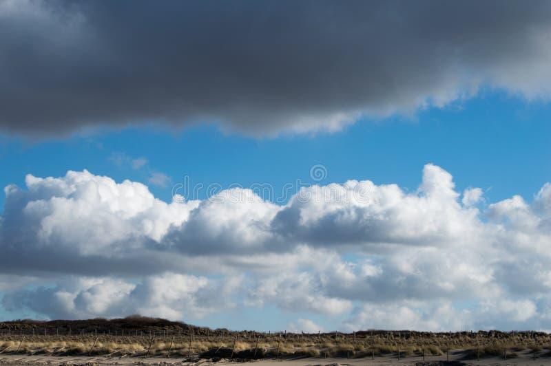Nuvole in una bella formazione della nuvola sopra le dune fotografia stock libera da diritti