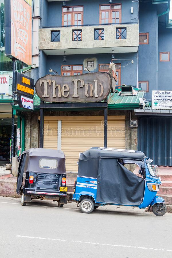 NUWARA ELIYA, SRI LANKA - JULI 17, 2016: Tuk tuks framme av baren i Nuwara Eliya släp royaltyfri foto