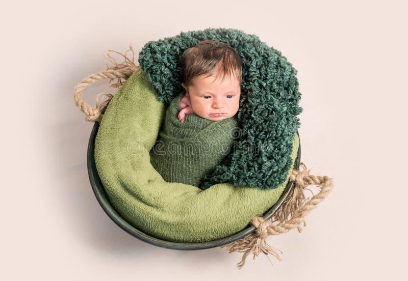 Nwborn wickelte im grünen coccon, das auf Korb liegt lizenzfreie stockfotos