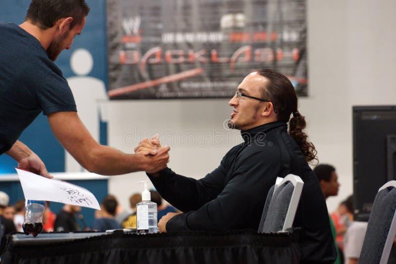 NXT atracam-se as mãos dos fãs das agitações de Neville após ter assinado a foto fotos de stock