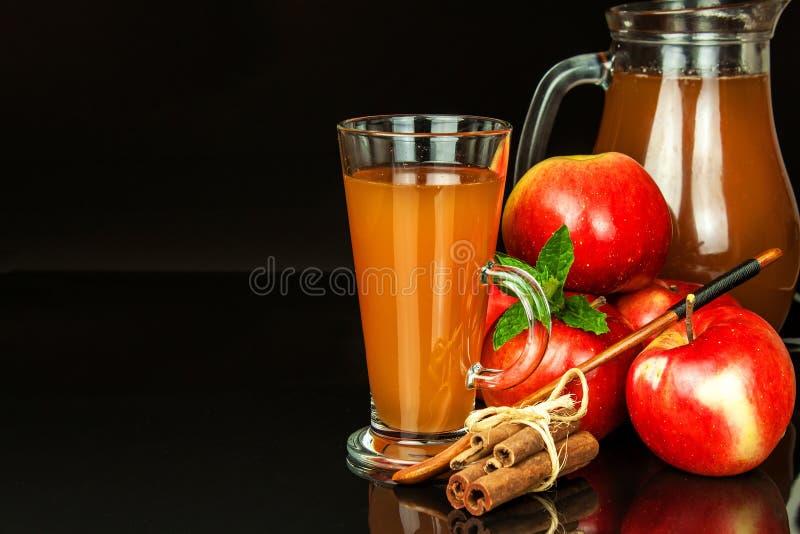 Ny äppelmust i ett exponeringsglas Sund dryck för fruktskörd Äpplen på köksbordet Produktion av fruktsaft På en svart backgr fotografering för bildbyråer