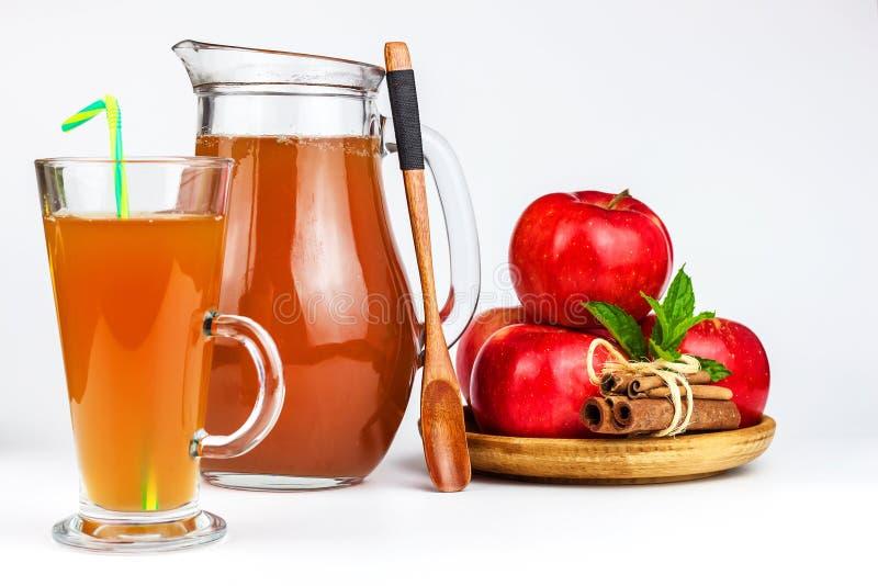 Ny äppelmust i ett exponeringsglas Sund dryck för fruktskörd Äpplen på köksbordet Produktion av fruktsaft på en vit backgr arkivfoton