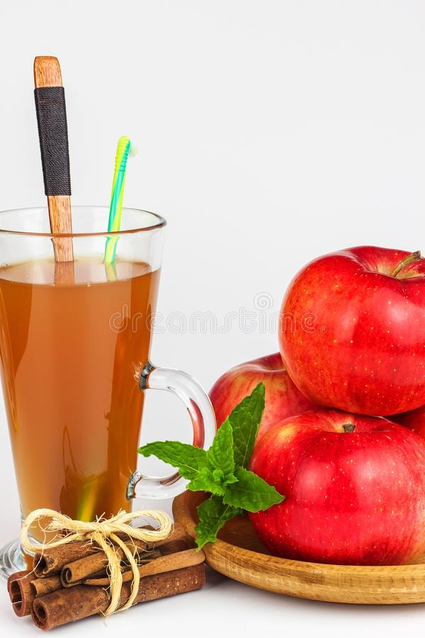 Ny äppelmust i ett exponeringsglas Sund dryck för fruktskörd Äpplen på köksbordet Produktion av fruktsaft på en vit backgr arkivbilder