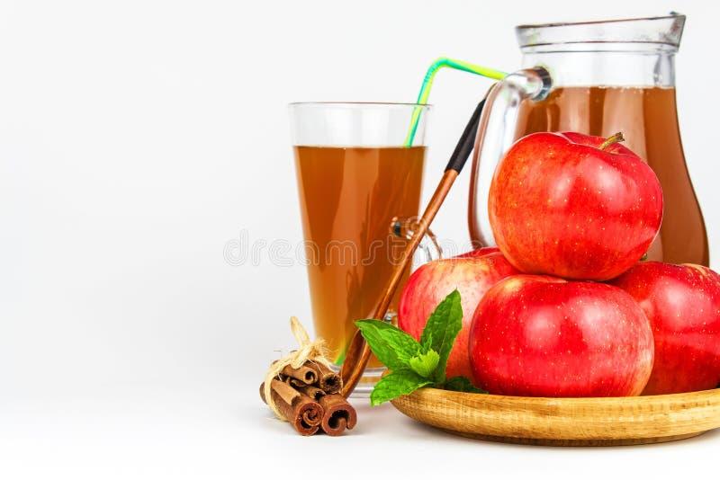 Ny äppelmust i ett exponeringsglas Sund dryck för fruktskörd Äpplen på köksbordet Produktion av fruktsaft på en vit backgr arkivbild
