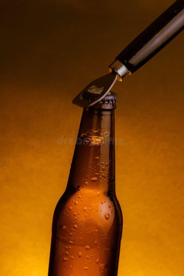 Ny ölflaska för kallt öl med droppar och propp som är öppen med flasköppnaren royaltyfri fotografi