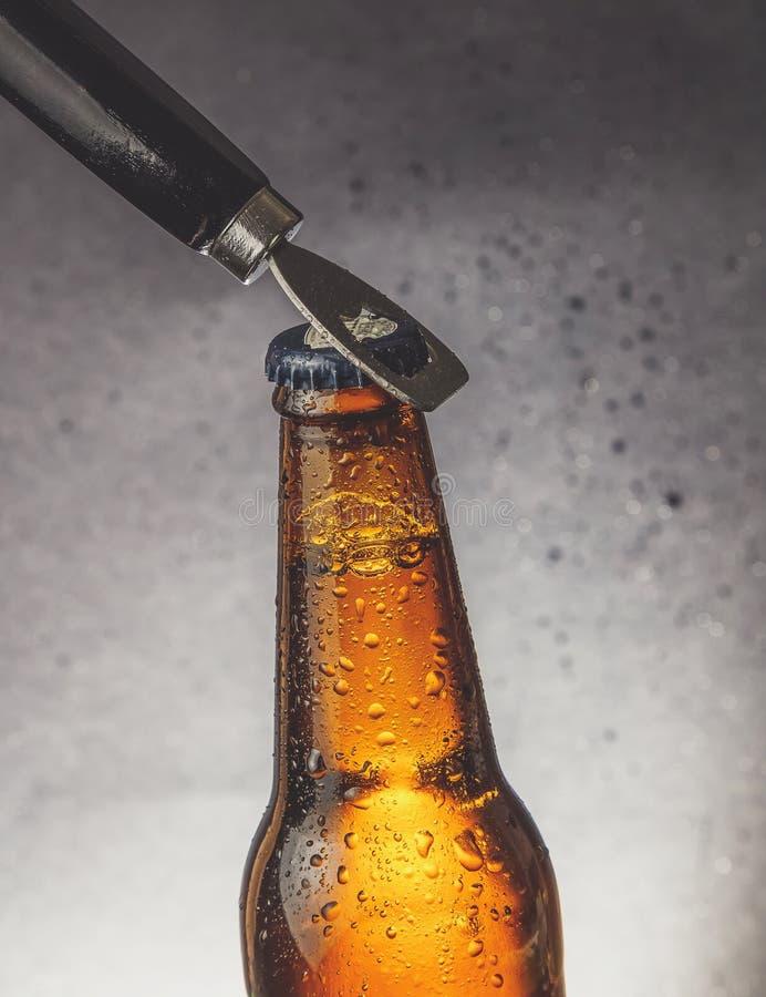 Ny ölflaska för kallt öl med droppar och propp som är öppen med flasköppnaren arkivfoton