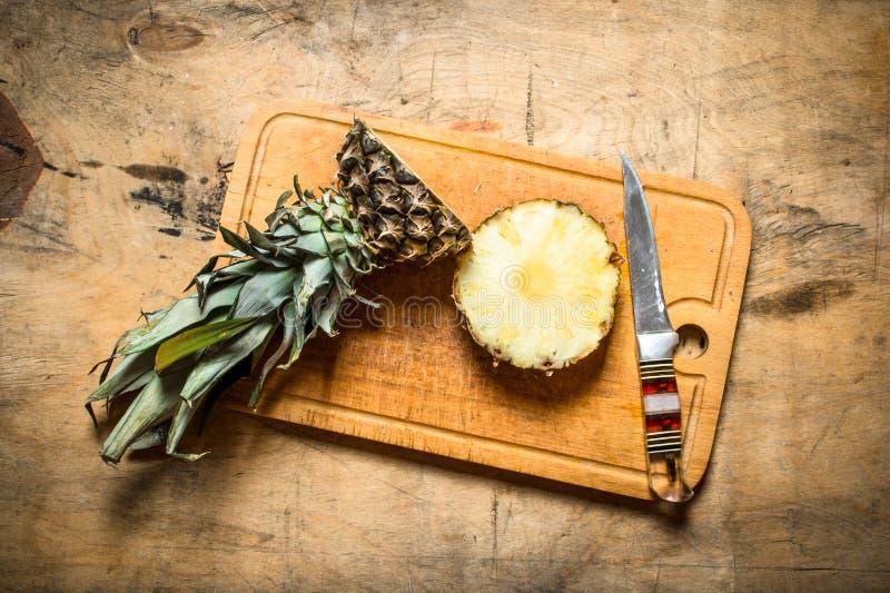 Ny ananas med en kniv arkivbild