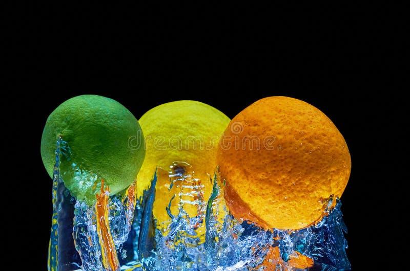 Ny apelsin, lyme, citron som faller i vatten med färgstänk på svart bakgrund fotografering för bildbyråer