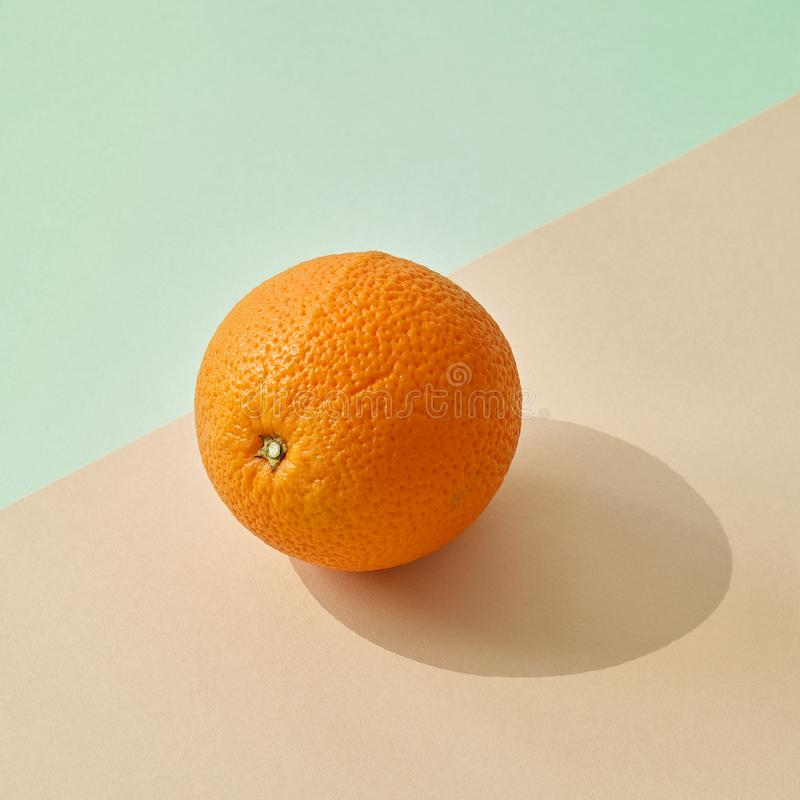 Ny apelsin på kulör pappers- bakgrund royaltyfri foto