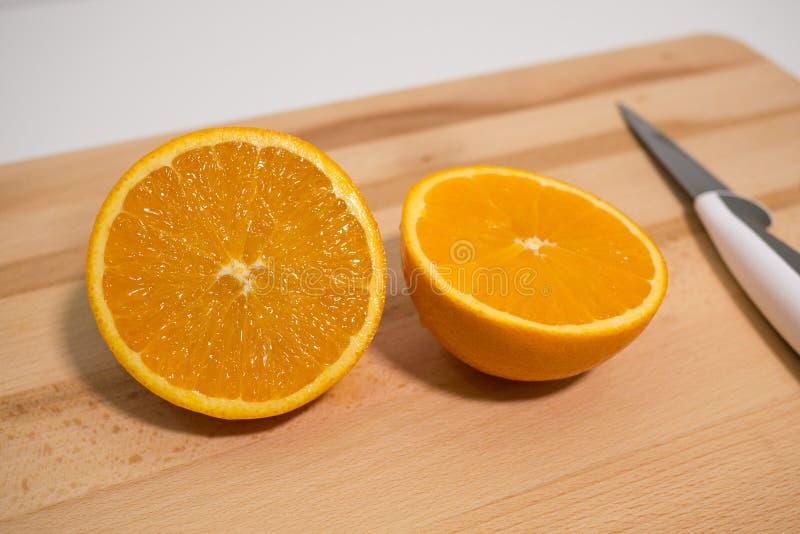 Ny apelsin som skivas i halva på träbräde med kniven royaltyfria foton