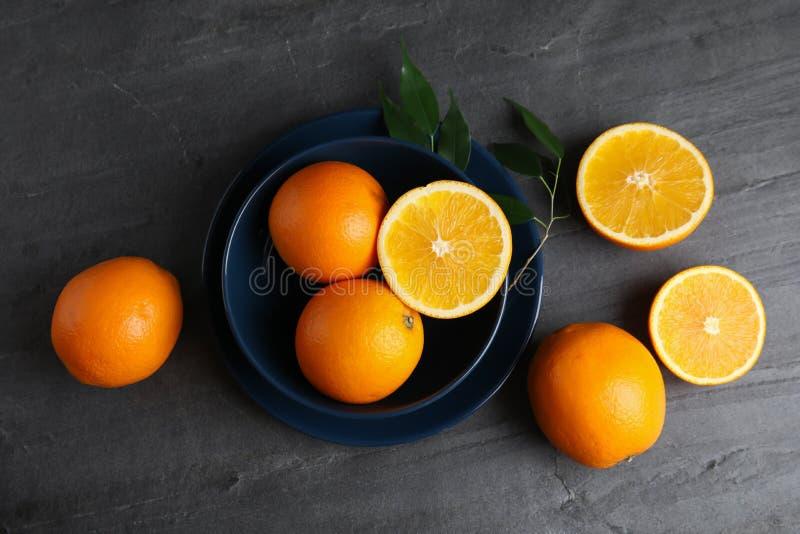 Ny apelsiner och bunke på den gråa tabellen royaltyfri foto